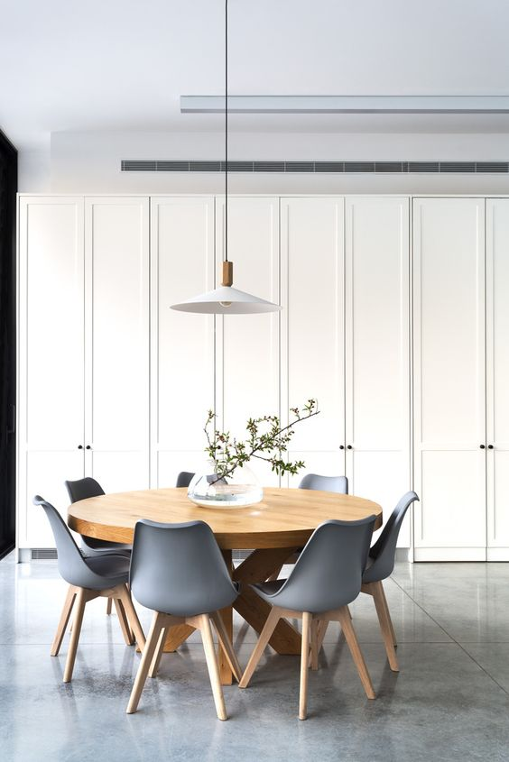 dining room, grey marble floor tiles, white cupboards, white wall ceiling, round wooden dining table, blue modern chairs with wooden legs, white pendant