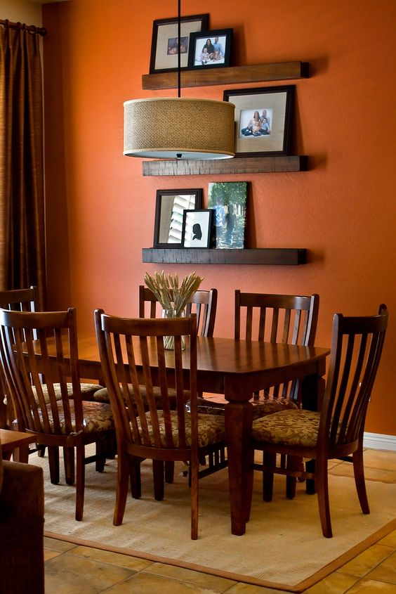 dining room, orange wall, brown floor tile, dark wooden dining table set, rattan round cover pendant