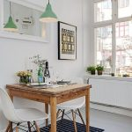 Dining Room, White Wooden Floor, Black Rug, Wooden Table, White Midcentury Modern Chairs, White Wall, Green Pendant, Mirror, Windows
