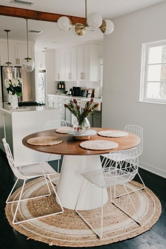 dining room with kitchen in dark floor, round wooden table, white wired modern chairs, pendant