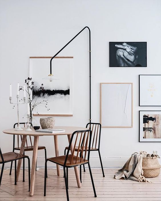 dining room, wooden floor, white wall, round wooden dining table, wooden dining chairs, black tall floor lamp