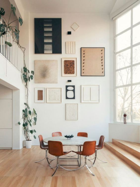 dining room, wooden floor, white wall, wall decorations, white round dining table, warm orange chairs, large glass windows
