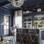 Elegant Bar, Pattern Flooring Tiles, Black Bar Island With Beige Top, Black Shelves, Acrylic Stool With Golden Legs, Chandelier