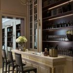 Elegant Indoor Bar, Marble Floor, Off White Bar Island With Golden Accent, Black Stool With Back, Chandelier, Wooden Built In Shelves For Wine