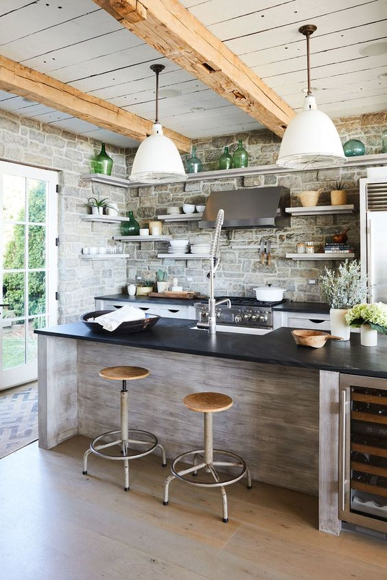 farmhouse kitchen, wooden floor, ashen wooden look on islan with black top, open brick wall, wooden ceiling, wooden beam, white cover pendant, floating shelves