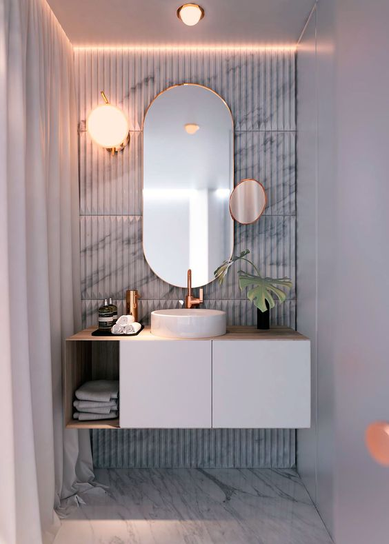 floating white vanity with wooden counter top, wooden shelves, mirror on the accent wall, white cink, orange glass sconce