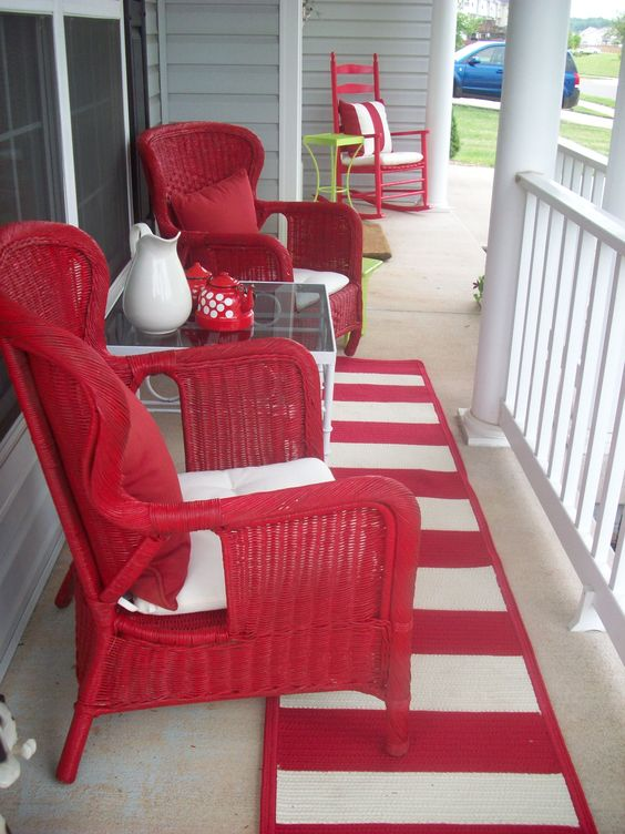 front porch, beige floor, red rocking chair white cushion, red rattan chairs white cushions, red pillows, square coffee table with glass top, red white stripes rug