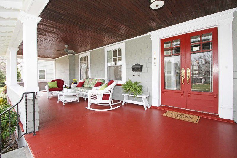 front porch, red wooden floor, white chairs, white rocking chairs red cushion, white sofa, white coffee table, white bench, grey wall, wooden ceiling, red door