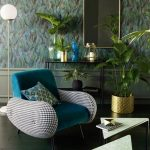 Green Velvet Chair With Plaid Arm Rest, Black Floor, Green Wall, Triangle Coffee Table, Plants, Black Simple Console Table