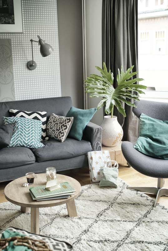 grey office chair with smooth surface, wooden floor, rug, grey sofa, small round wooden coffee table, grey curtain, plant