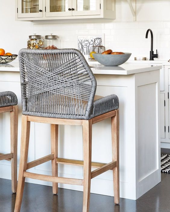 grey woven stool on wooden egs, brown cushion, white island, grey floor, white subway tiles