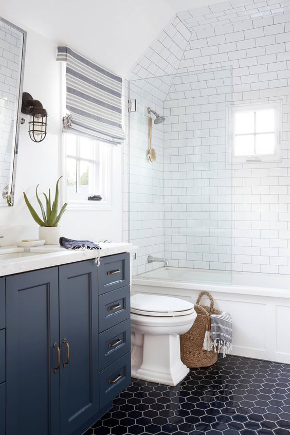 guest bathroom with white subway tiles on shower area with arch ceiling, white tub, white toilet, black hexagon floor tiles, grey wooden vanity with white top, roman shade on window