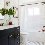 Guest Bathroom With White Subway Wall Tiles, Tiny White Black Geometric Floor Tiles, White Tub, White Toilet, White Wall, Black Wooden Vanity With White Top, Mirror, White Curtain