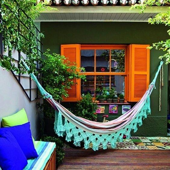 hammock with green big fringe, wooden floor, green wall, orange window, olorful cushion on wooden bench