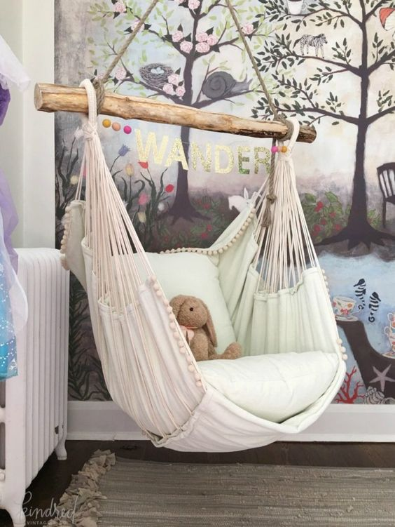 hanging chairs in bedroom with cushion, wooden support, wooden floor, rug, white wooden crib
