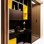 Home Office Area With Built In Table, Cabinet, And Shelves In Black And Yellow, Black Chair