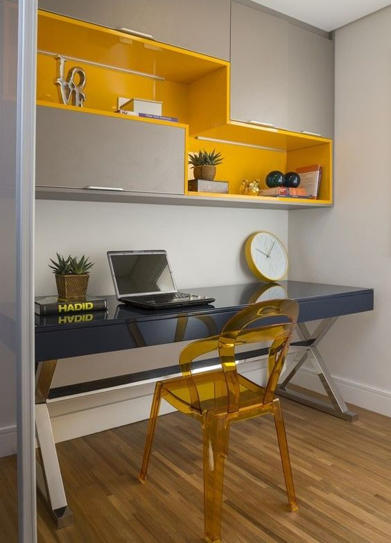 home office area with grey table, yellow acrylic chair, grey cabinet with yellow shelves