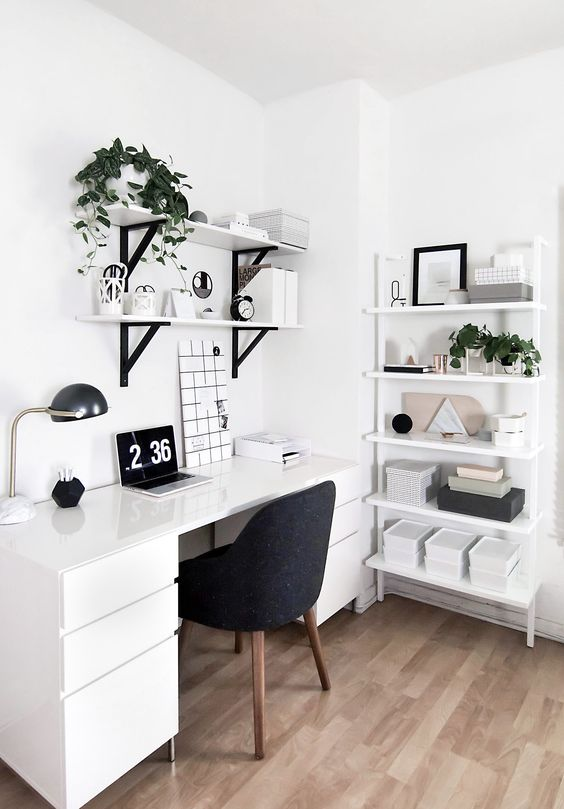 home office in the corner with white table with drawers, white floating sheles, white shelves, table lamp, black chair