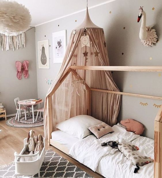 kids bedroom, brown raw low bed with house shaped, wooden floor, grey wall, fluffy pendant, small table chairs, grey rug,
