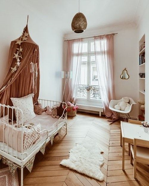 kids bedroom, chevron wooden floor, white wall ceiling, white iron bed platform, mauve canopy, wooden table and chairs, white modern chair, built in shelves, pink curtain, pendant