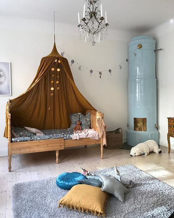 kids bedroom, grey rug, wooden sliding bed platform, brown canopy, blue fireplace, white wall, chandelier