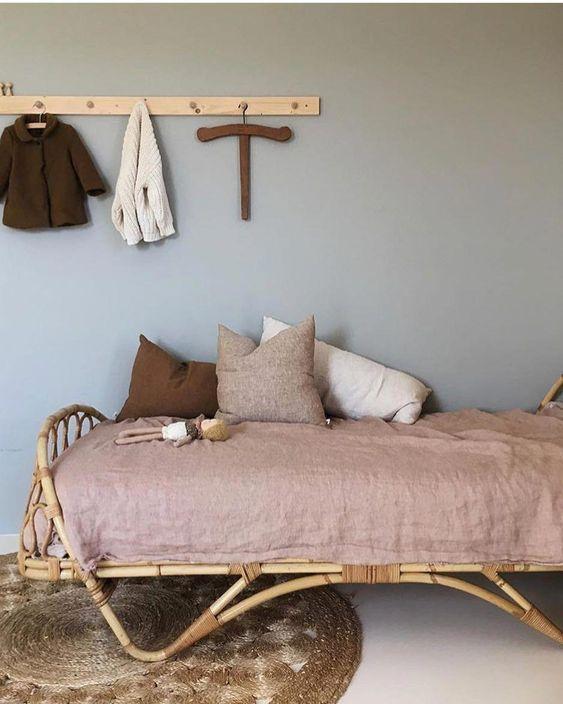 kids bedroom, rattan bed, beige bedding, pillows, white floor, rattan rug