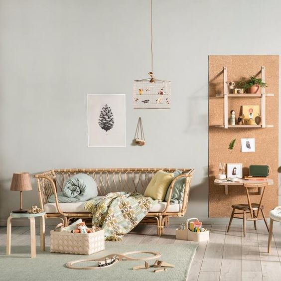 kids bedroom, rattan sofa bed, green rug, wooden floow, light grey wall, study area with orange wall, floating wooden table and shelves, wooden chair