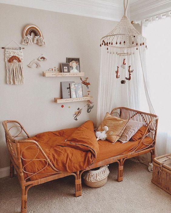 kids bedroom, rug flooring, beige wall, floating shelves, wall decortaion, white bohemian canopy, rattan bed, orange linene