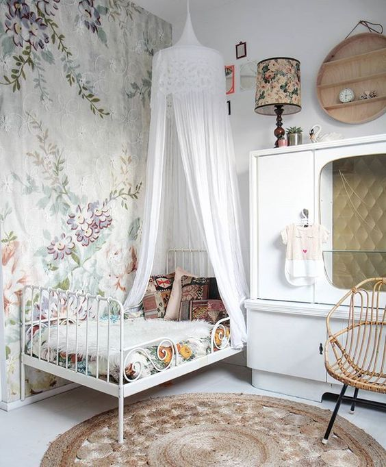kids bedroom, white iron bed, white floor, white wall, flowery wallpaper, white canopy, white cabinet, rattan chair