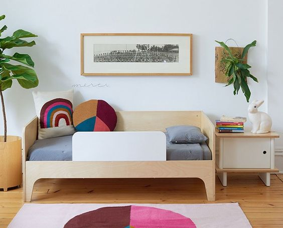kids bedroom, white wall, wooden floor, white rug, wooden bed with secure board, wooden side table, plants
