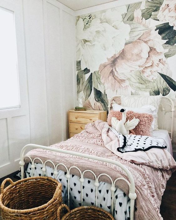kids room, wooden floor, white wooden wall, flower wallpaper, rattan baskets, white iron bed, white pnik bedding, wooden side table