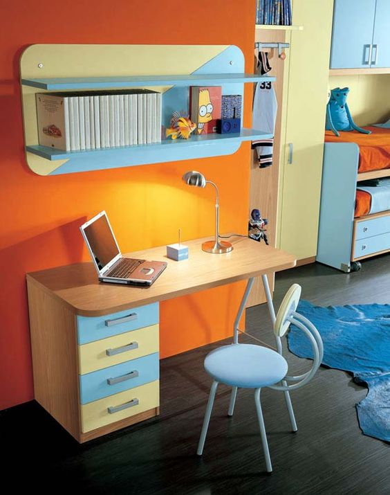 kids study space, orange wall, wooden table with blue yellow drawers, blue yellow floating shelves, blue chair