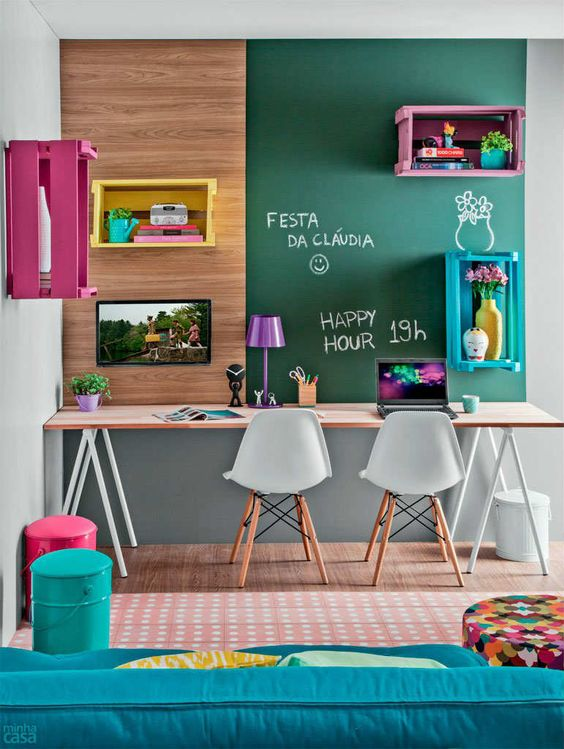kids study space with long modern wooden table with white legs, white modern chairs, wooden panel board on the wall, floating boxes for shelves, green board