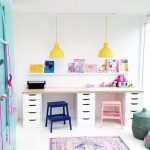 Kids Study Space With Long Wooden Table, White Drawers, Blue And Pink Stool Chairs, Yellow Pendants, White Wooden Floating Shelves