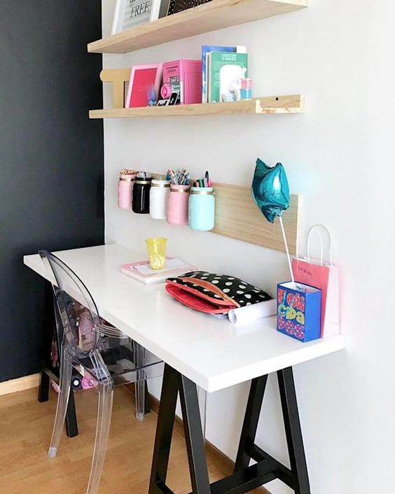 kids study space with white wall, white table black legs, floating wooden shelves, wooden board rail, acrylic chair