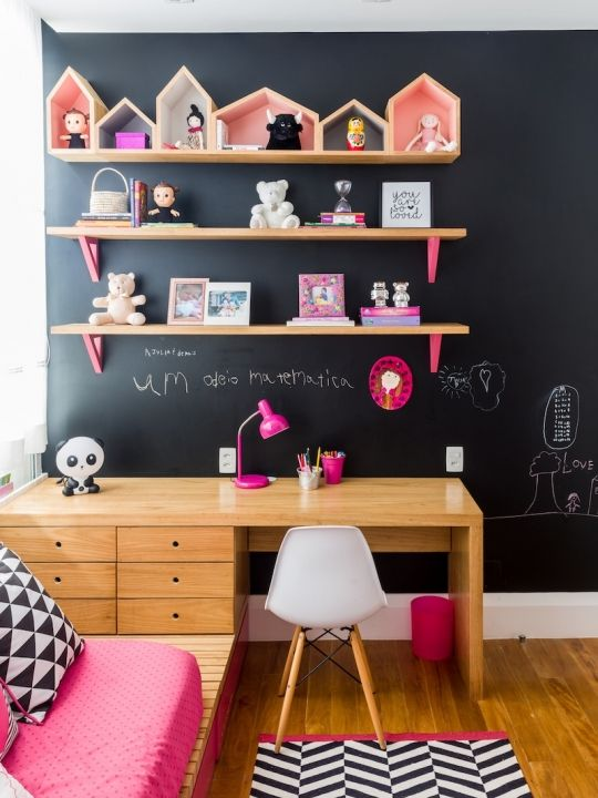 kids study space with wooden table with drawers, floating wooden shelves with pink support, house shaped desoration, white modern chair