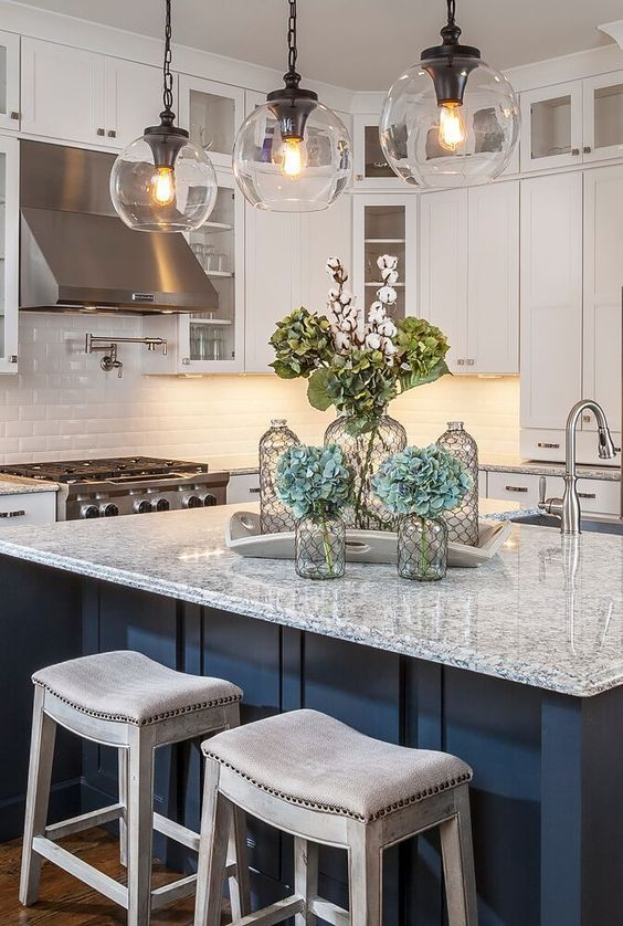 kitchen, blue island with blue marble top, glass pendants, white cabinet, white backsplash tiles