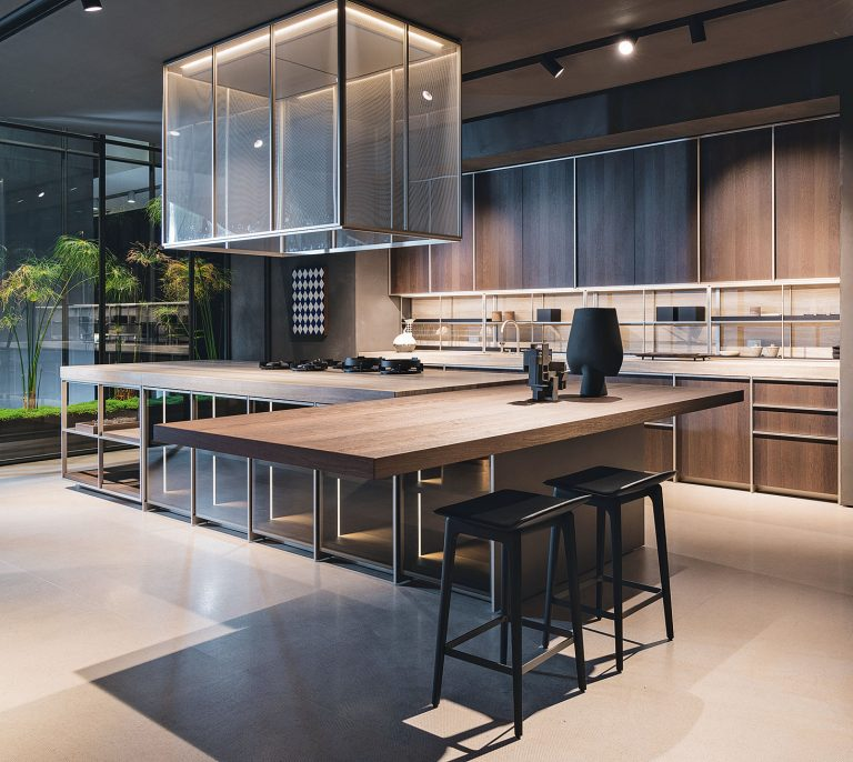 kitchen, brown floor, brown wooden floating island, glass cage island with wooden top, glass square cage pendant, wooden cabinet, white top