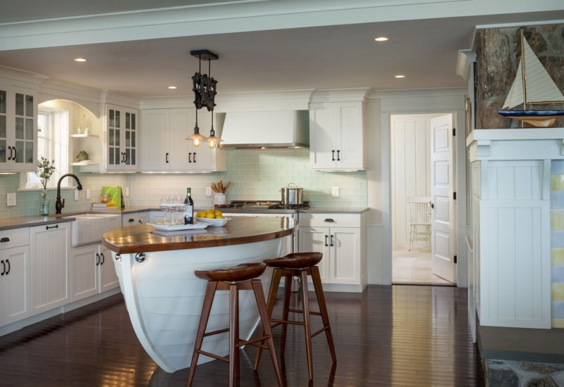 kitchen, dark wooden floor, wooden stools, white wooden boat shaped island with brown wooden top. white cabinets, grey countertop, white wall, white cupboards, white ceiling