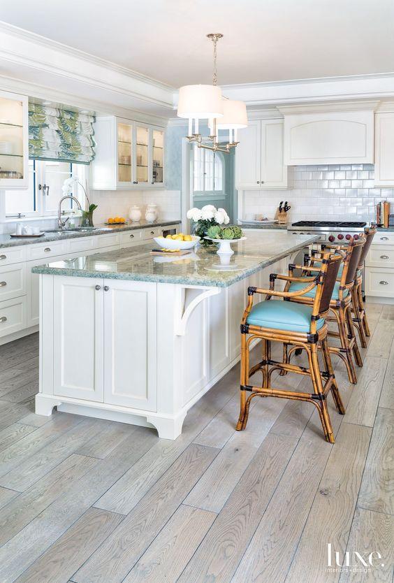 kitchen, light wooden floor, white cabinet, white wooden island, white wall, white subway backsplash ,rattan high shairs blue cushion, blue marble top