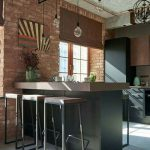 Kitchen, Open Brick Wall, Chevron Floor, Black Island With Brown Top, Matching Stools, Black Cabinet, Brown Roman Shade, Glass Pendants, Round Black Chandelier