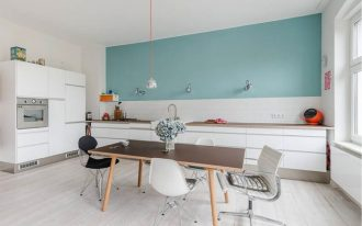 kitchen, white bottom cabinet, white wooden floor, white backsplash, green wall, sconces, dining table set, modern chairs, pendant, white cupboard