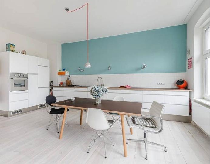 kitchen, white bottom cabinet, white wooden floor, white backsplash, green wall, sconces, dining table set, modern chairs, pendant, white cupboard