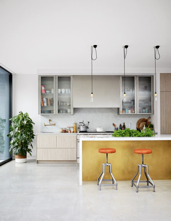kitchen, white floor, white wall, white ceiling, off white cabinet, yellow siland with white op and side, orange stool, industrial naked pendants, lare glass wall