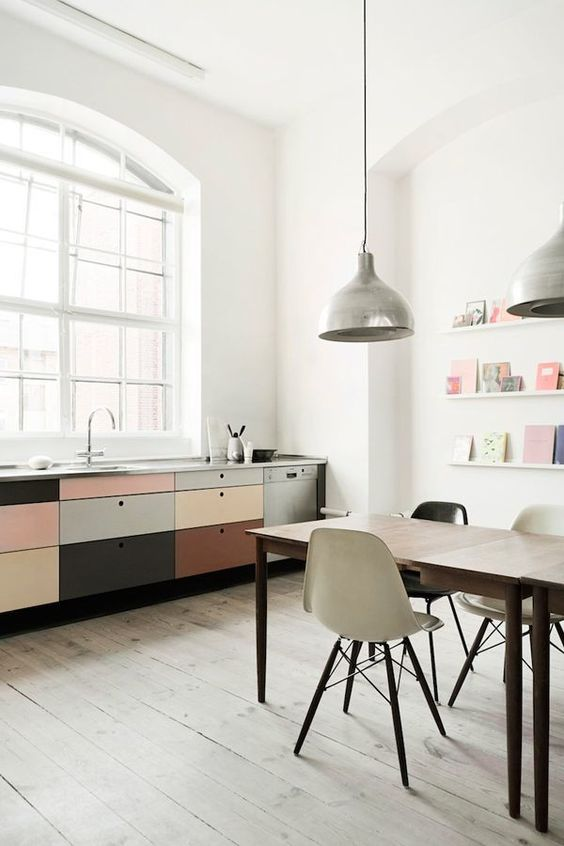 kitchen, white wall, large glass windows with white frames, soft colorful drawer fronts cabinet, modern dining table set, silver pendants, light wooden floor