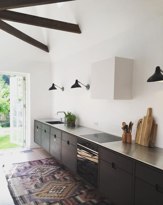 kitchen, white wall, sconces, black cabinet, silver top, rug, wooden beams on ceiling