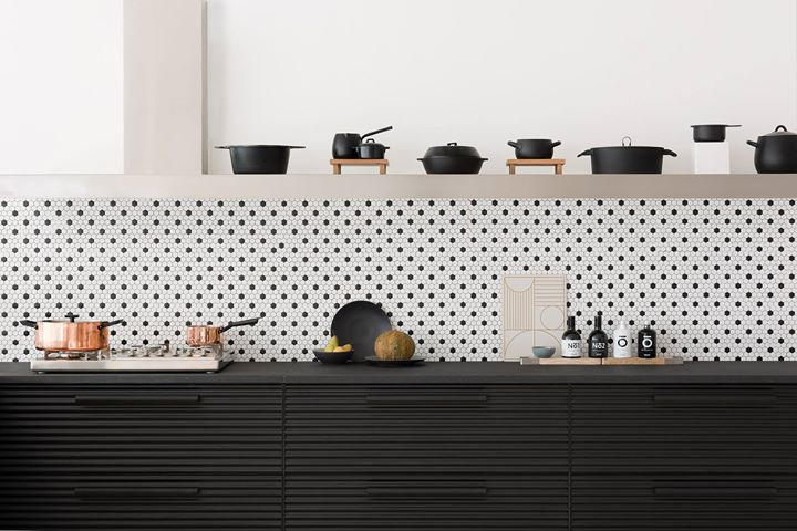 kitchen with black cabinet, tiny black white backsplash tiles, grey floating shelves