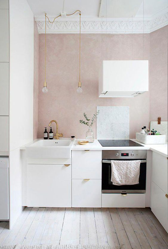 kitchen with no upper cabinet, white bottom cabinet, wooden floor, pink wall, pendants, white top, white sink