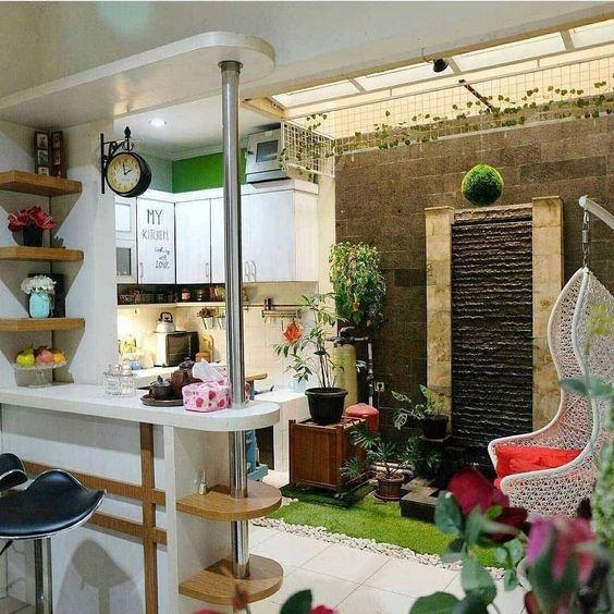 kitchen with white cabinet, white floor tiles, white bar island, black stools, small indoor garden, rattan swing
