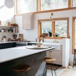 Kitchen With Wooden Floor, Black Island With White Porcelain Top, White Subway Tiles On Wall, Wooden Framed Windows, Wooden Stool With Metal Legs
